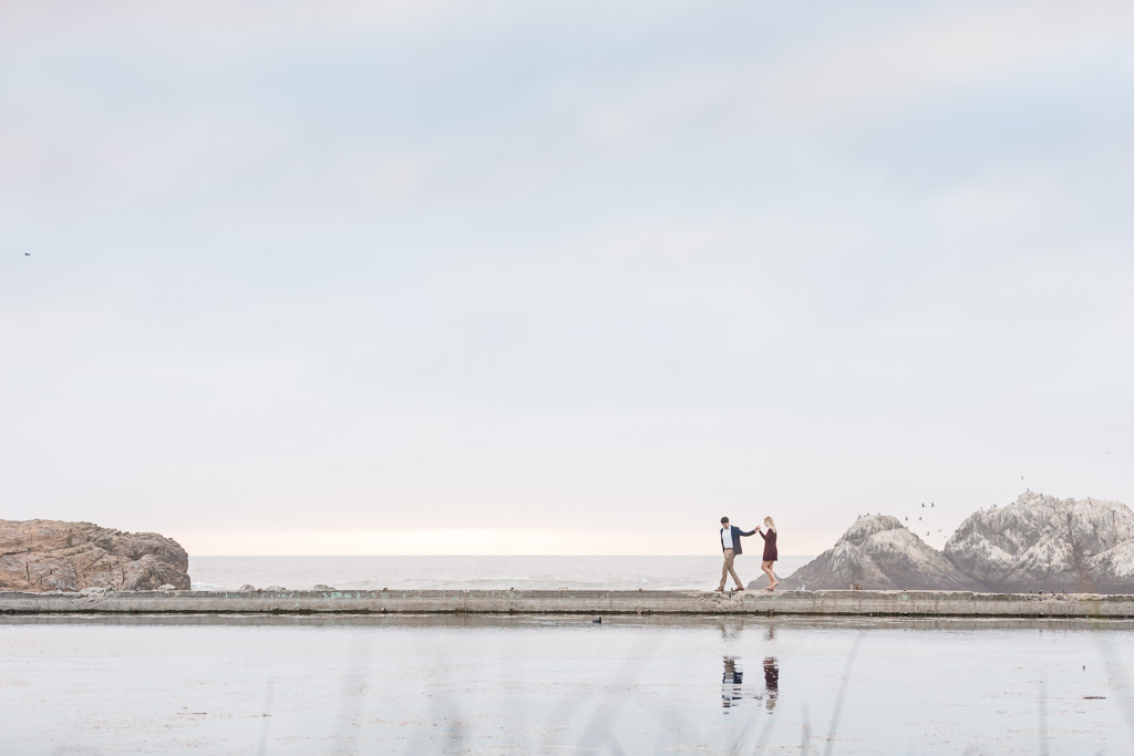 couple walking on the edge by the ocean