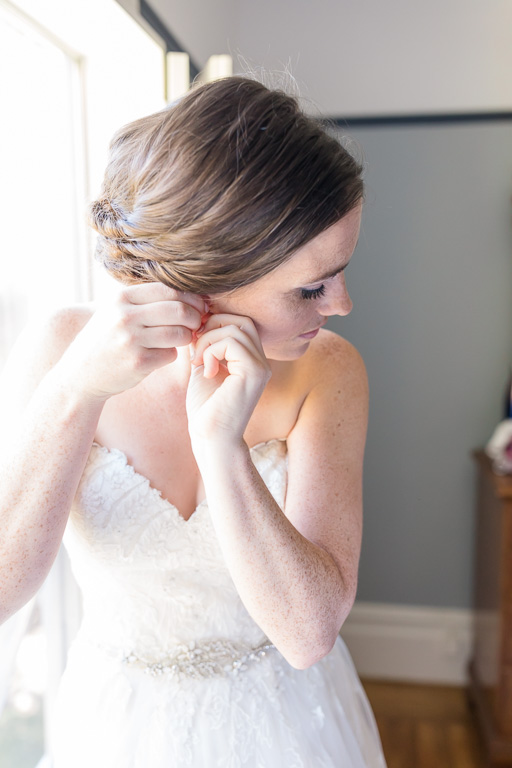 putting on the bridal earrings