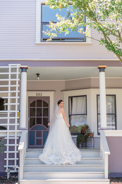 a back shot of the bride in front of the house they got ready at