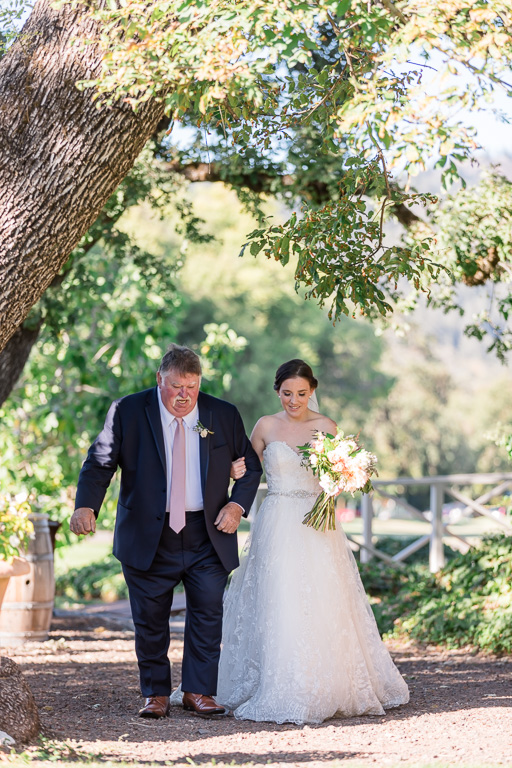 bride walks down the aisle escorted by father