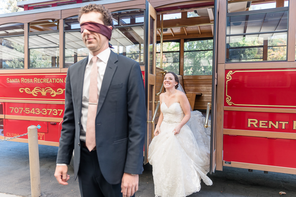 bride walks out of a trolley to surprise her groom