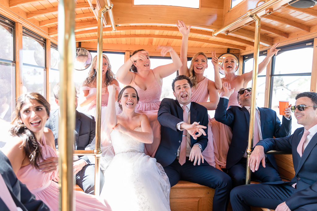 couple and wedding party having fun singing along to the rap songs on the trolley