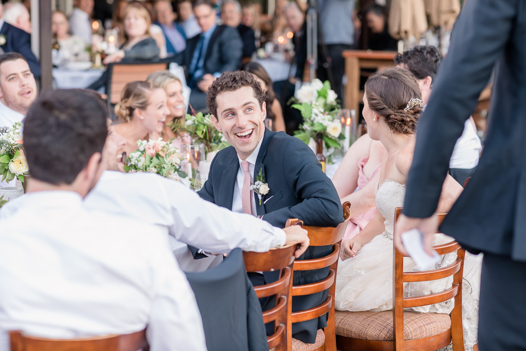 groom laughing at a hilarious toast