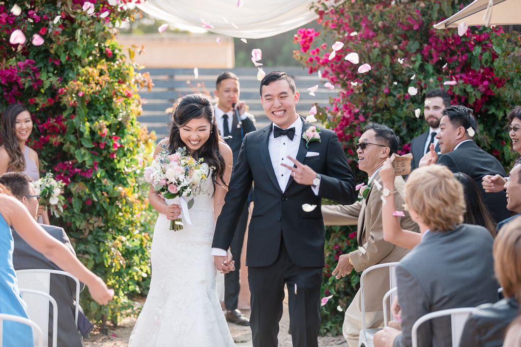 newlywed walking down the aisle with rose petals throwing at them - Aracely wedding ceremony