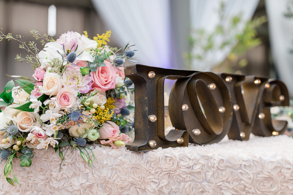 lit up love sign on sweetheart table