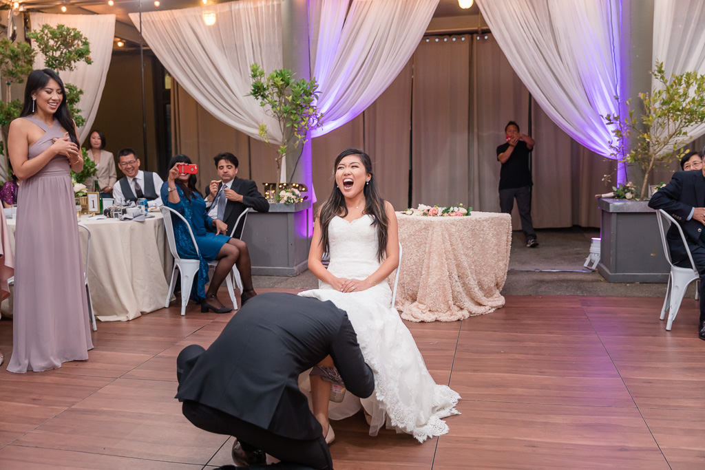 bride has a surprise for the groom during the wedding garter fetch