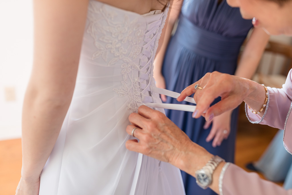 mom helping bride lace up the back of her dress