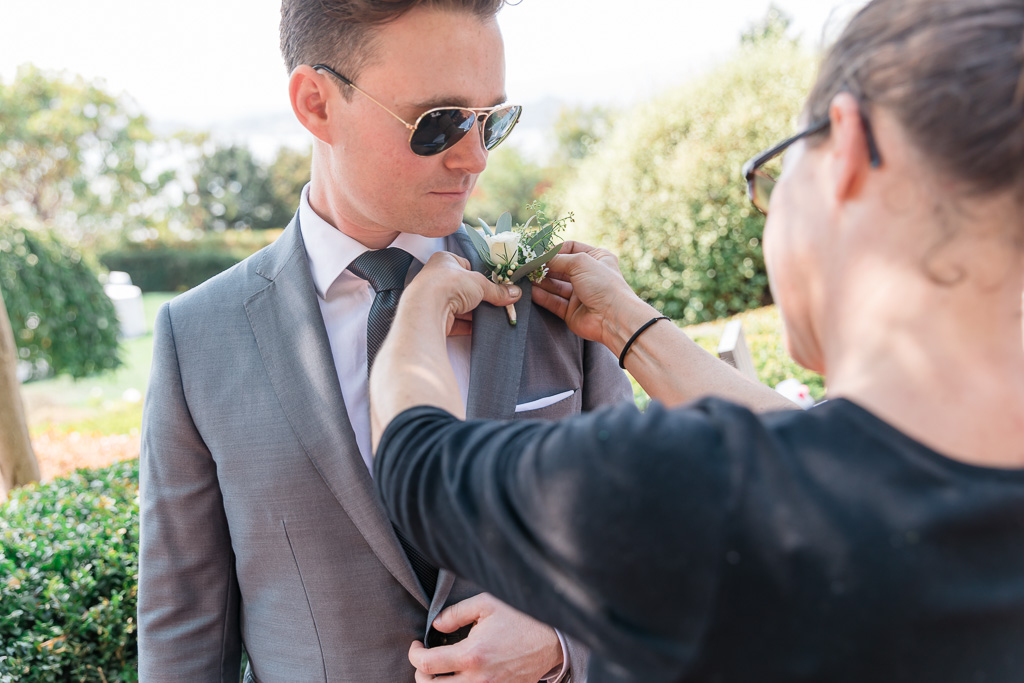 Groom getting boutonnière pinned on