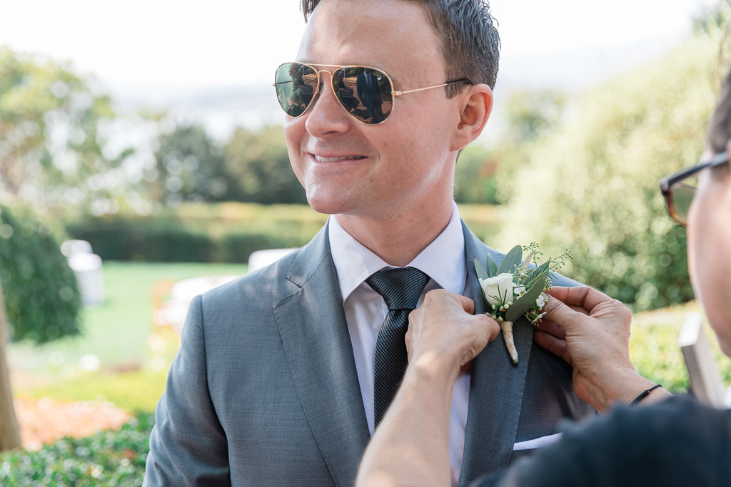 pinning boutonnière on the groom's suit jacket lapel