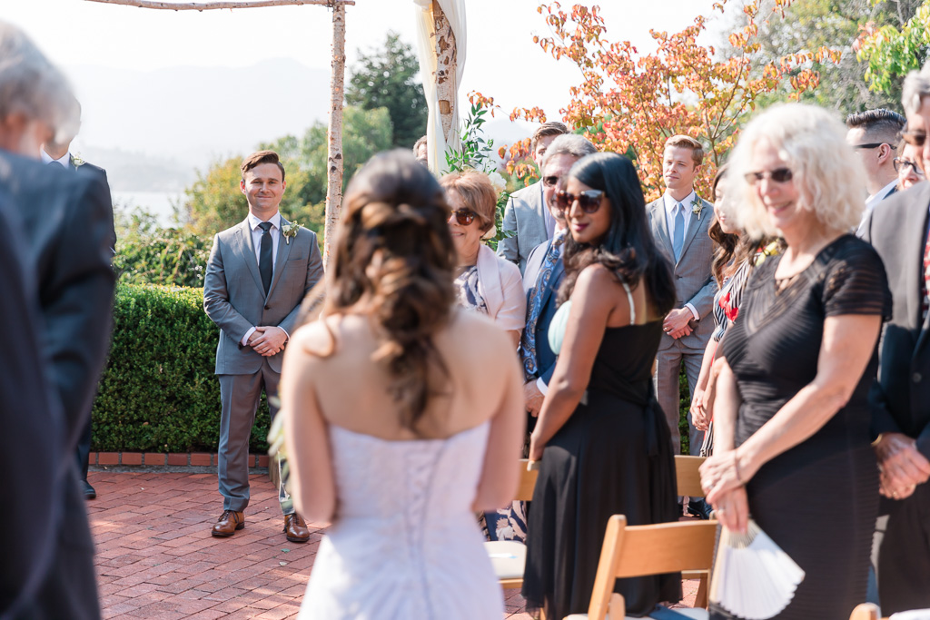 groom watching bride walk down the aisle towards him during ceremony