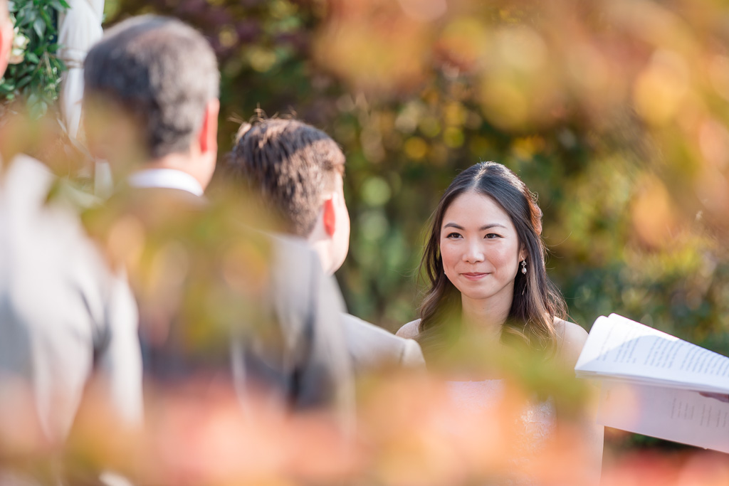 creative angle through tree leaves of photo of bride looking at groom during ceremony