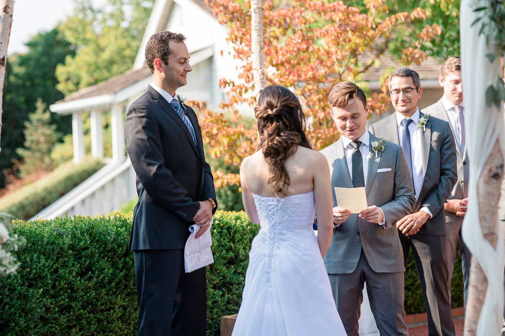 groom reading his handwritten vows during ceremony