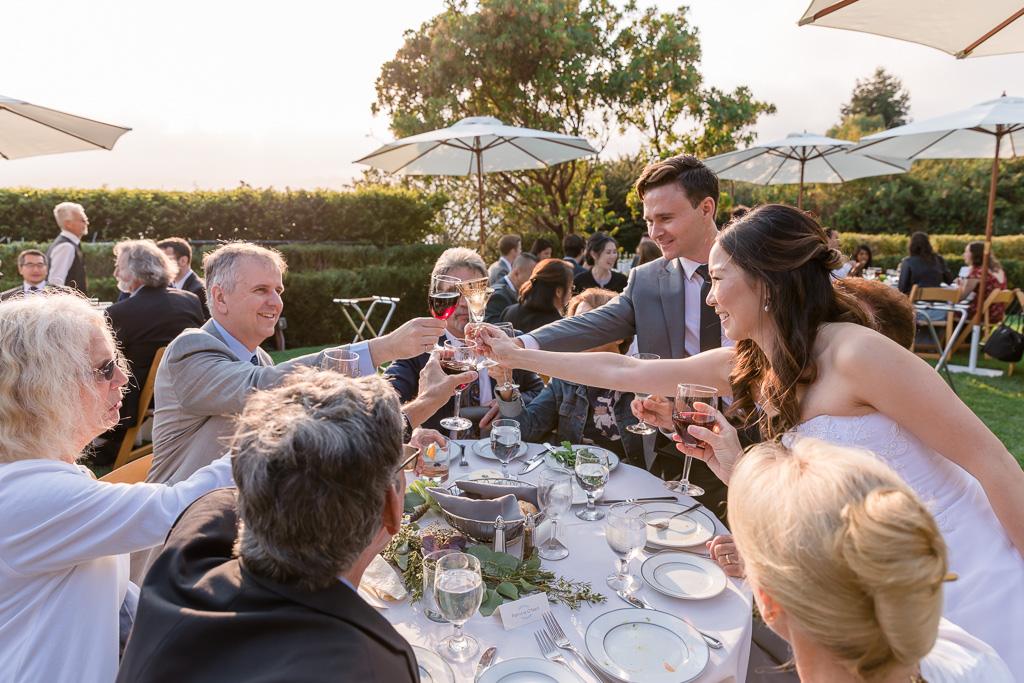 bride and groom visiting guest tables and sharing a glass