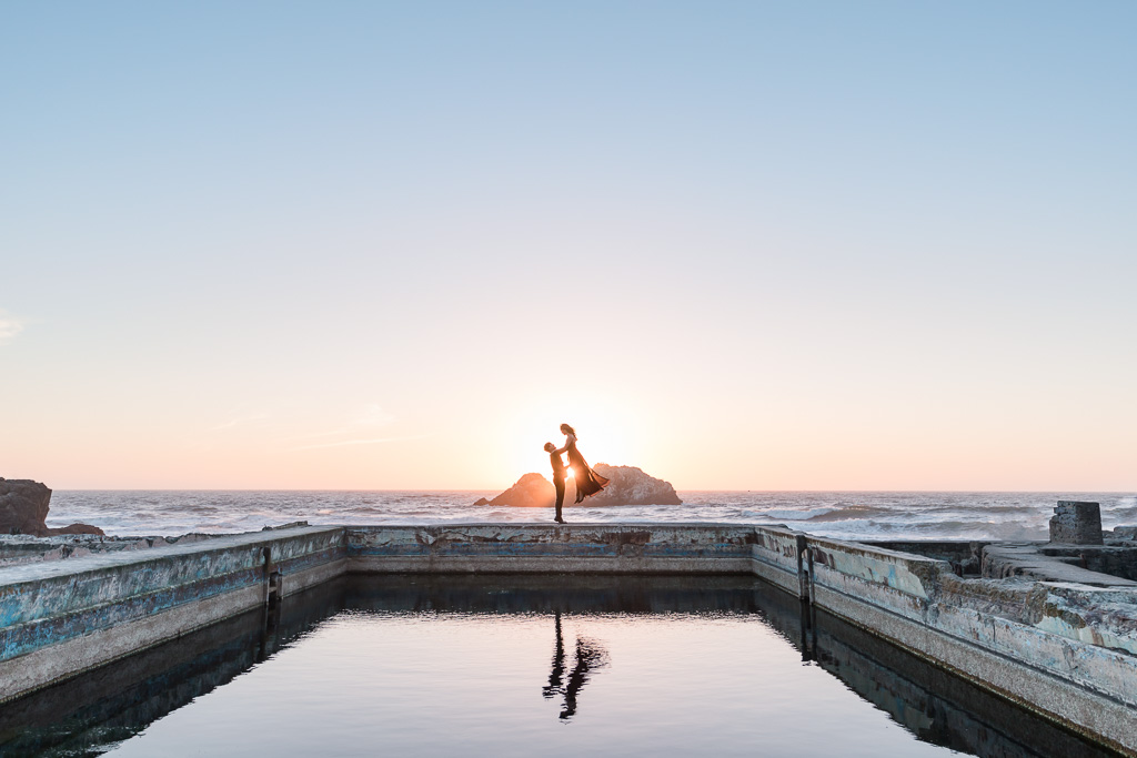 Sutro Baths sunset dance lift engagement photo with dress