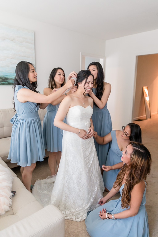 bridesmaids helping bride with her hair pieces