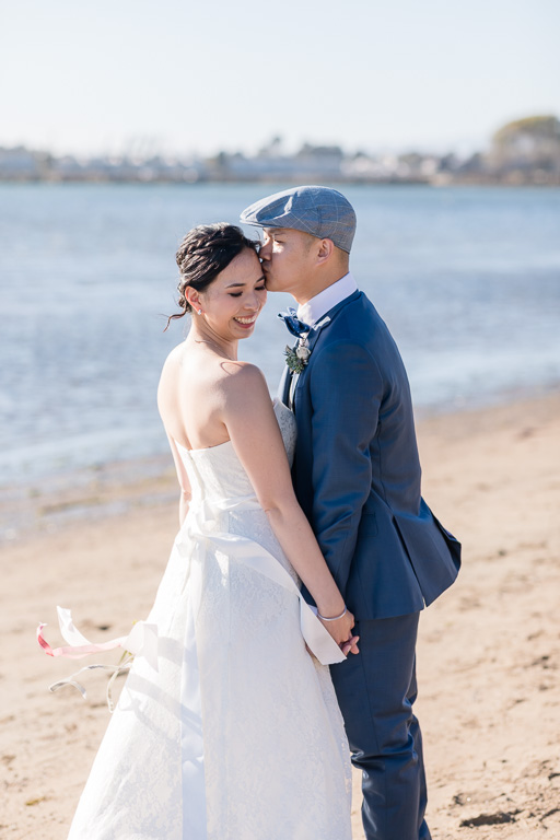 groom kissing bride's forehead at Crown Memorial State Beach