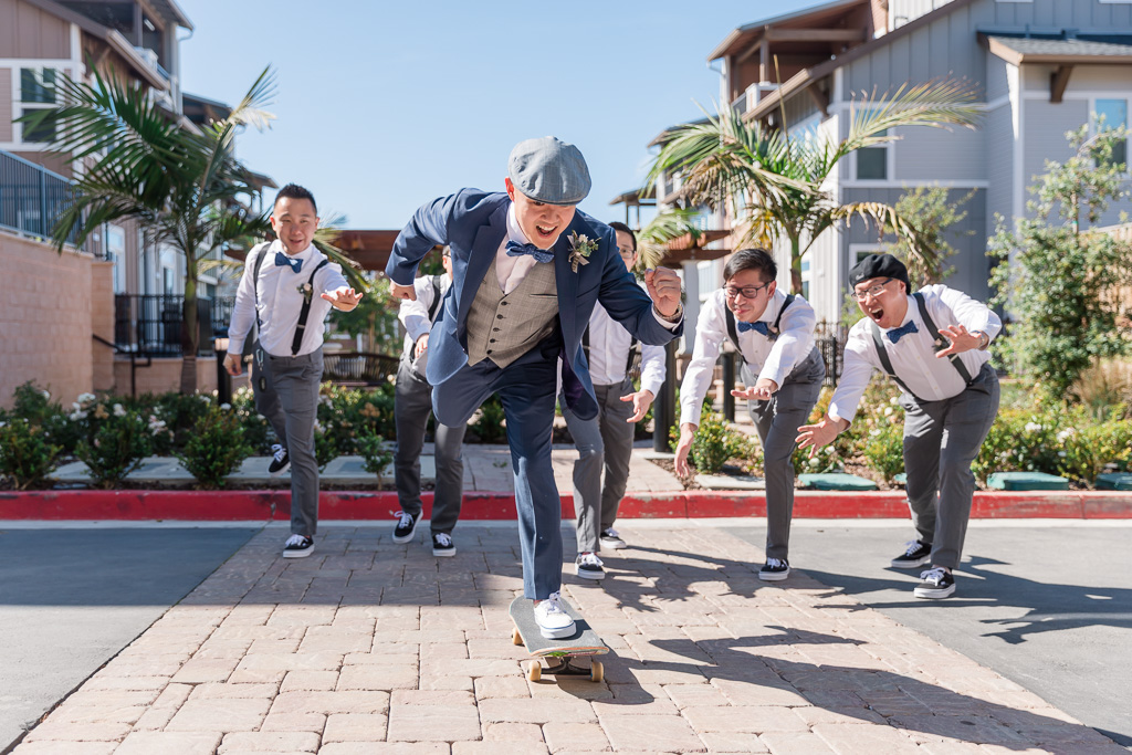 fun photo of groom on a skateboard with groomsmen behind him