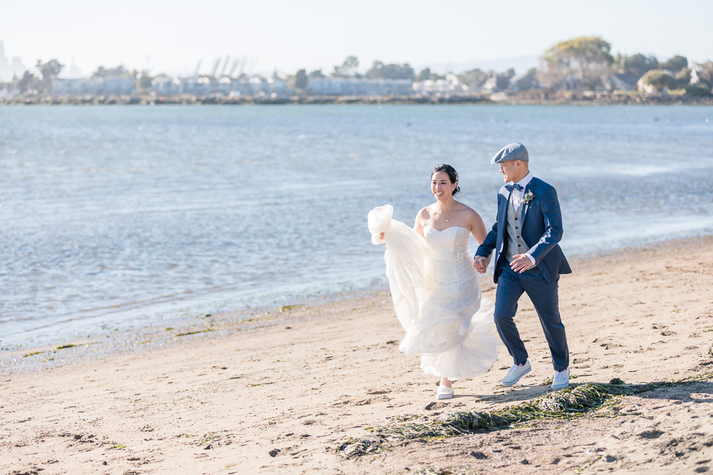 bride and groom walking along the beach with Alameda in the background