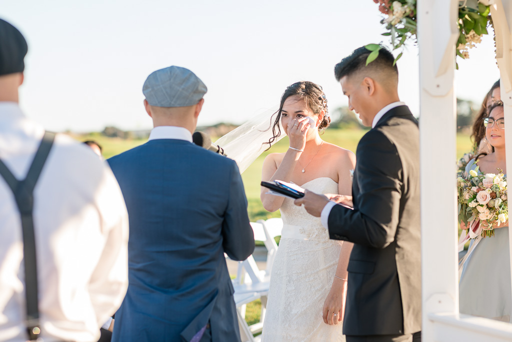 bride wiping away a tear during wedding ceremony