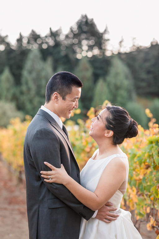 newlywed couple looking at each other lovingly in the vineyards