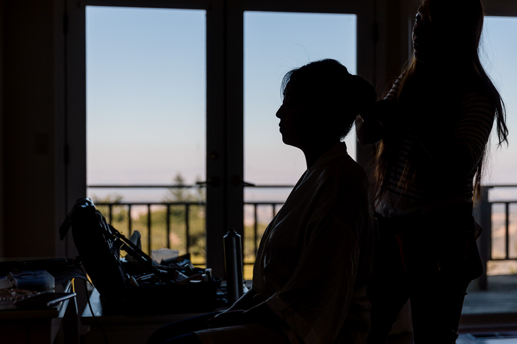 silhouette shot of the bride having her makeup done