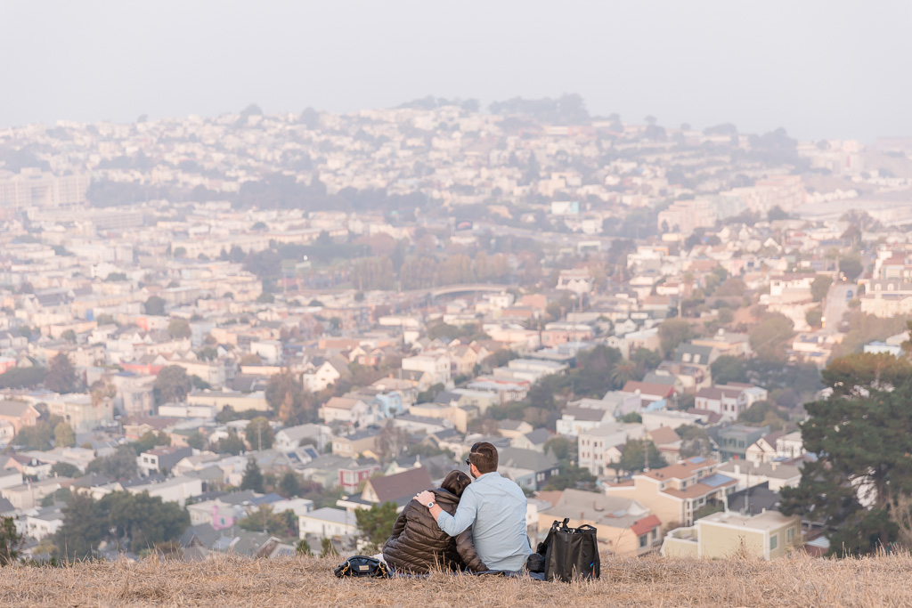 couple sitting on the hill enjoying the view of San Francisco