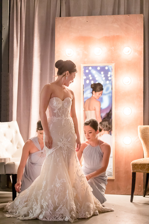 bridesmaids helping bride looking stunning in front of a mirror at the Winery SF