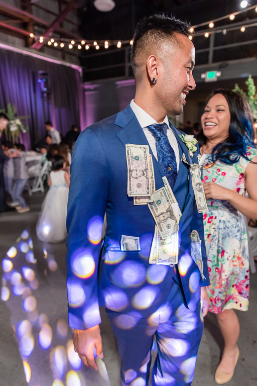 groom with lots of cash pinned during money dance
