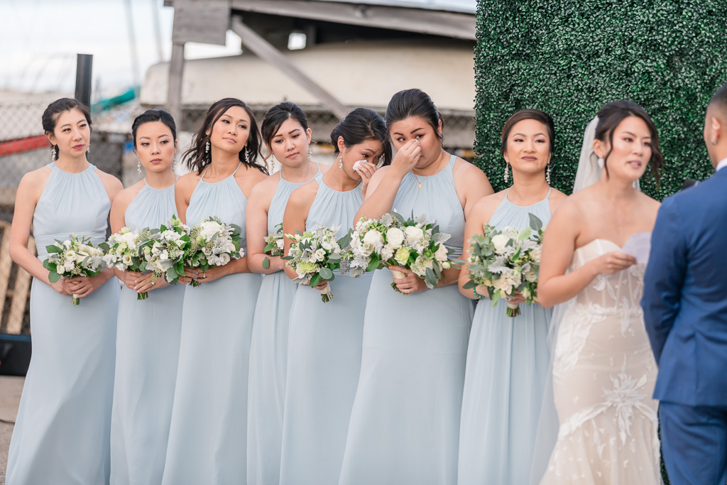 bridesmaids wiping tears during touching wedding ceremony