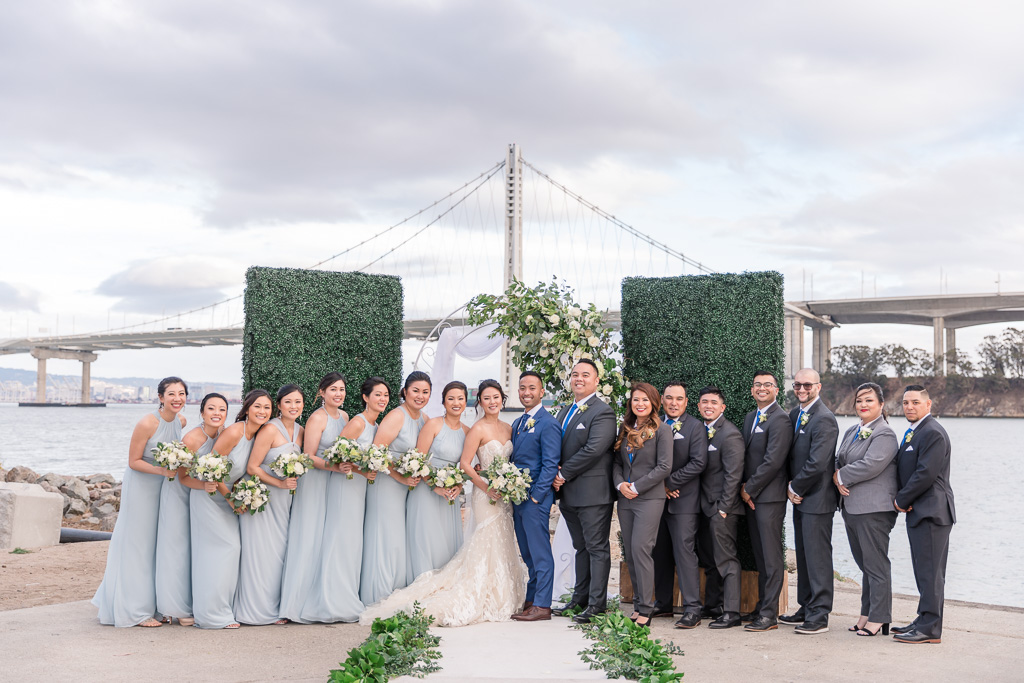 bridal party photo lined up in front of the Oakland Bay Bridge