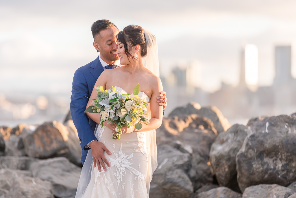 golden hour photo of bride and groom in front of San Francisco city skyline