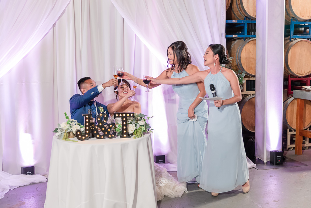 bridesmaids proposing a wine toast to the bride and groom