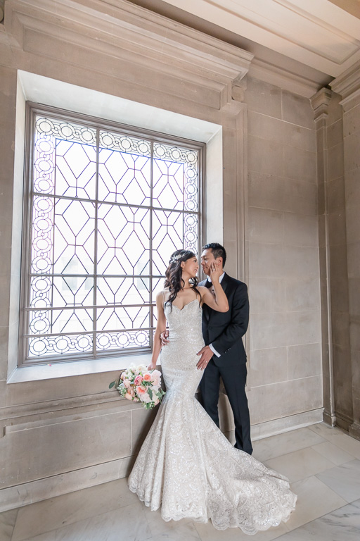 newlyweds by the San Francisco City Hall window