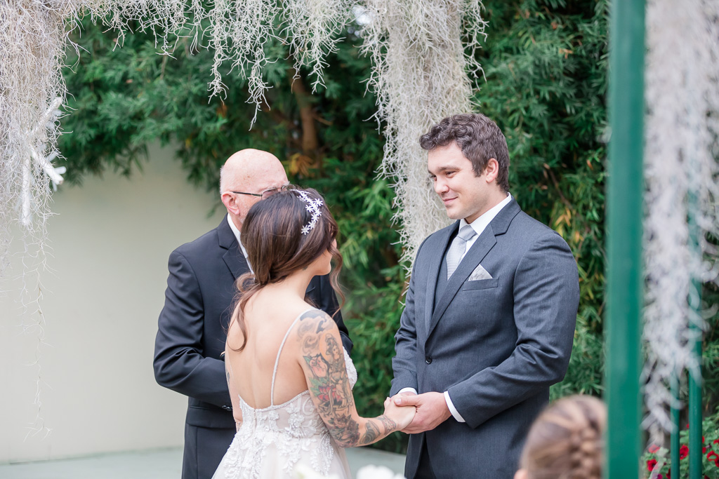 groom looking into bride's eyes during wedding ceremony