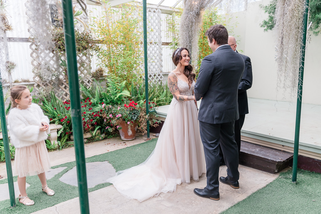 bride and groom being married inside a greenhouse