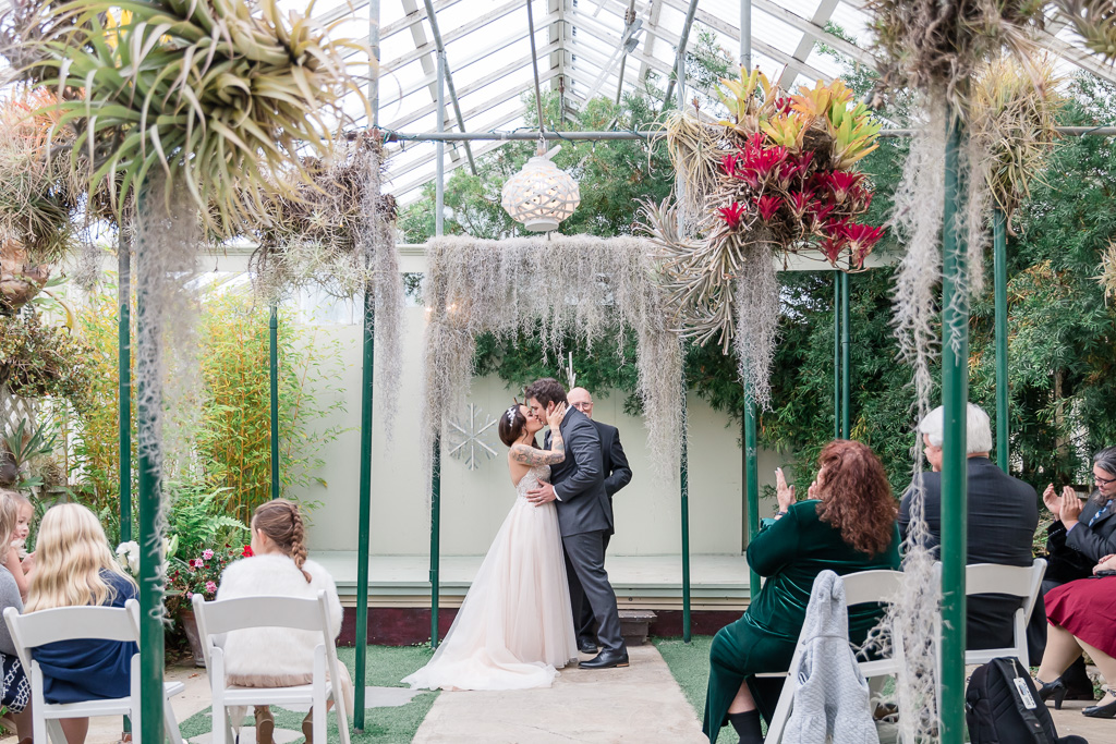 wedding ceremony first kiss inside a pretty greenhouse garden