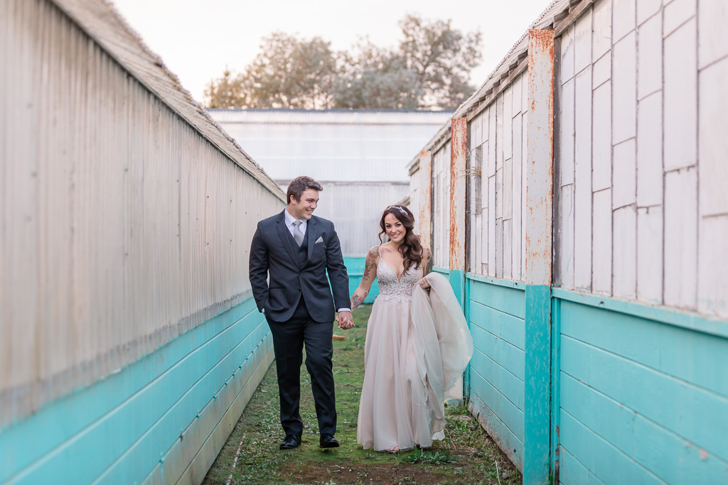 portrait of bride and groom walking between rustic buildings