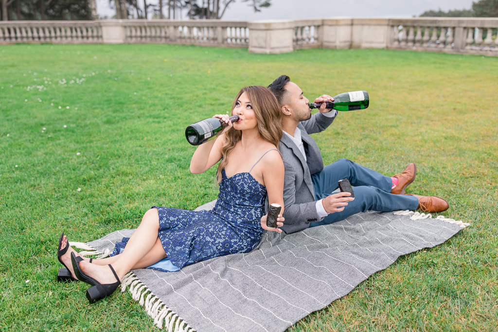 fun loving San Francisco couple taking engagement photos while drinking champagne straight out of a bottle and eating spam musubi