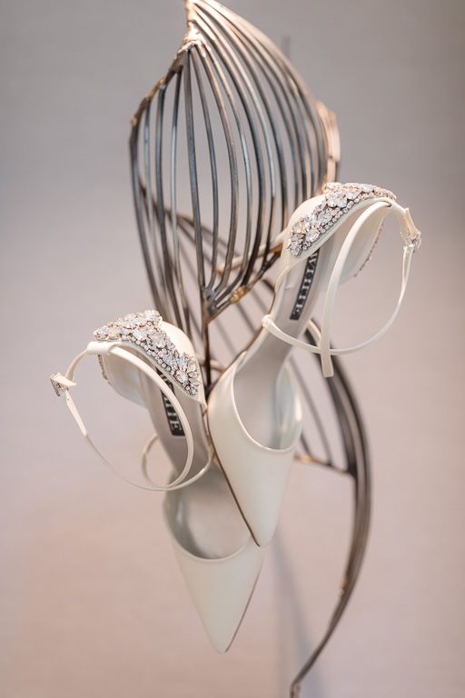artsy photo of the bridal shoes hanging on a sculpture