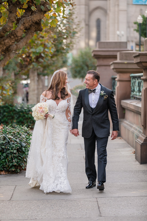 wedding couple walking on the sidewalk outside the Grace Cathedral and Fairmont