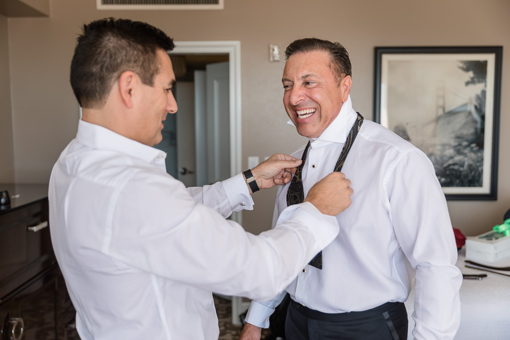 best man helping groom with his bow tie