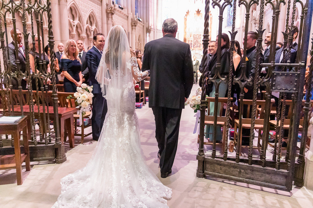 bride being escorted by father down the chapel aisle