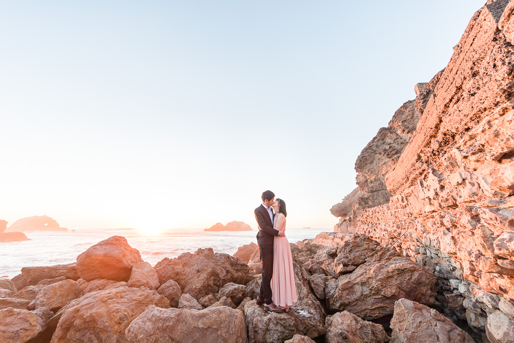 couple kissing under the sunset by the sea