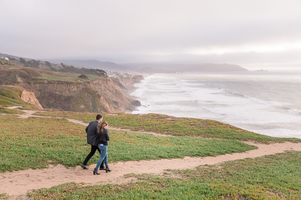 couple walking to the Pacific oceanside cliffs at Mussel Rock