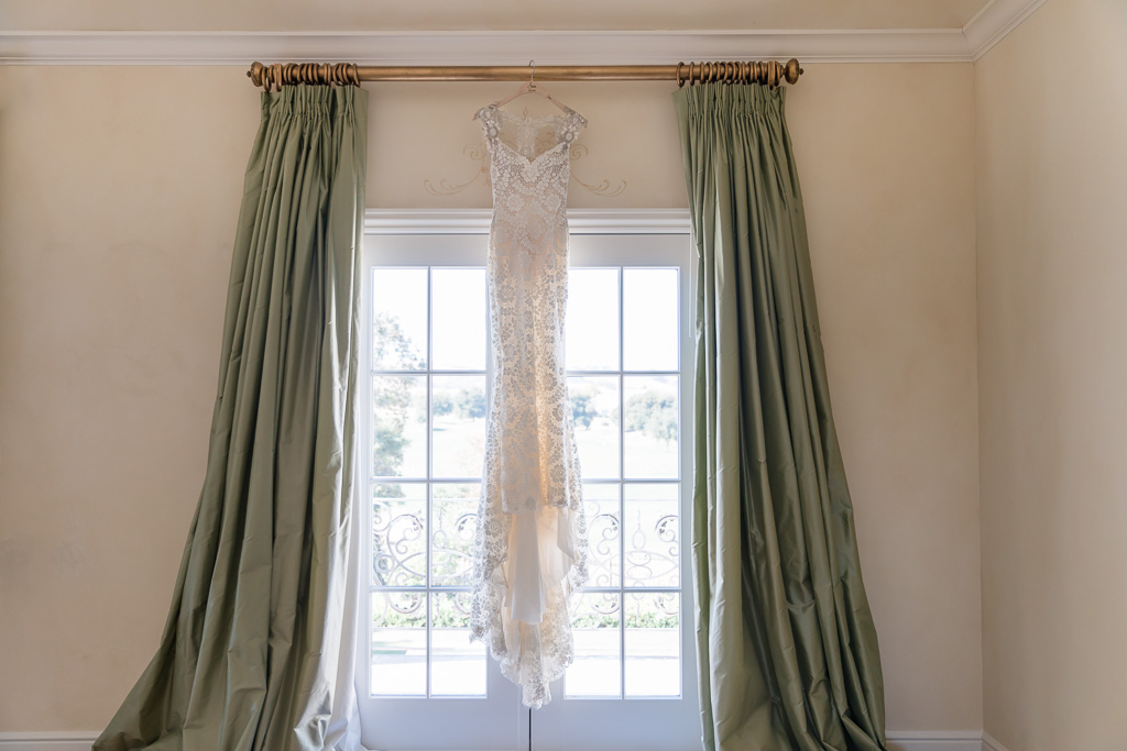 Galia Lahav wedding dress hanging on the floor to ceiling window