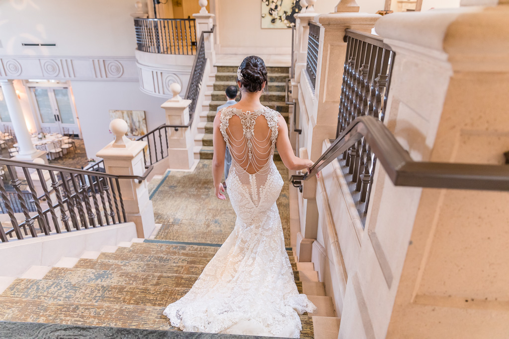 bride walking down the staircase for a first look with her groom