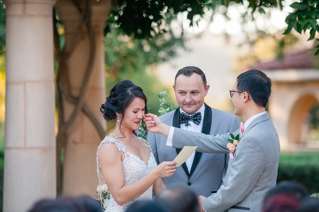 groom wiping away bride's tears during vow exchange