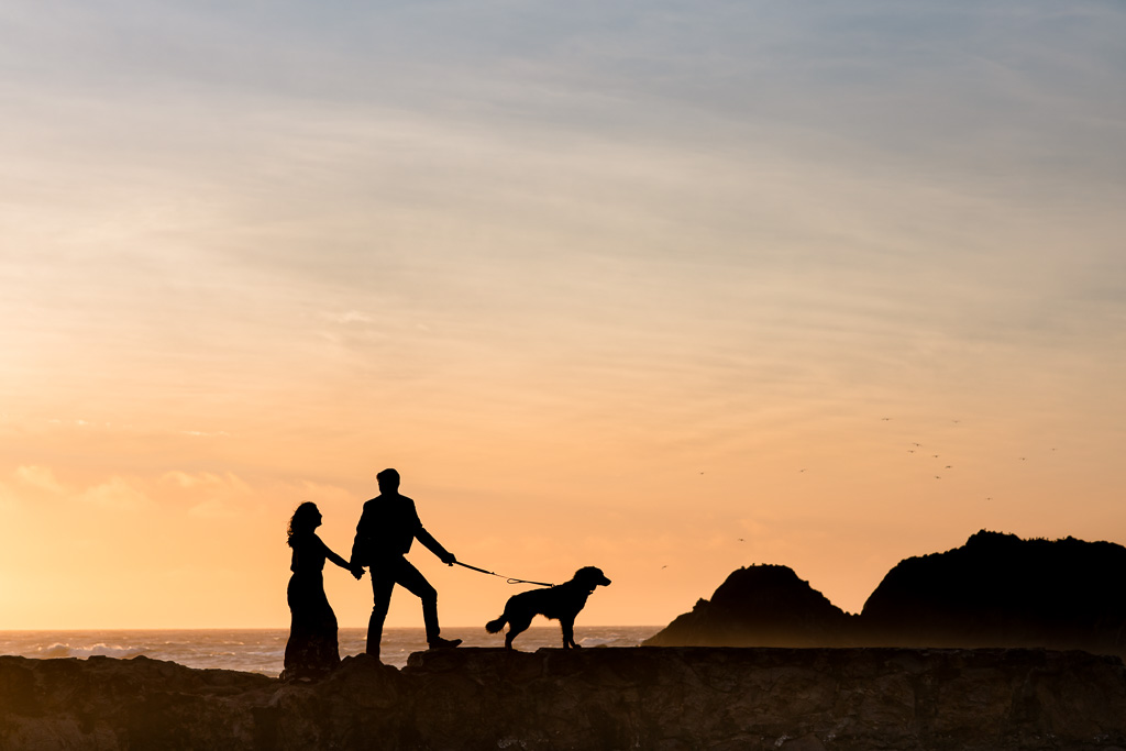 romantic silhouette engagement photo with a puppy by the Pacific Ocean in San Francisco