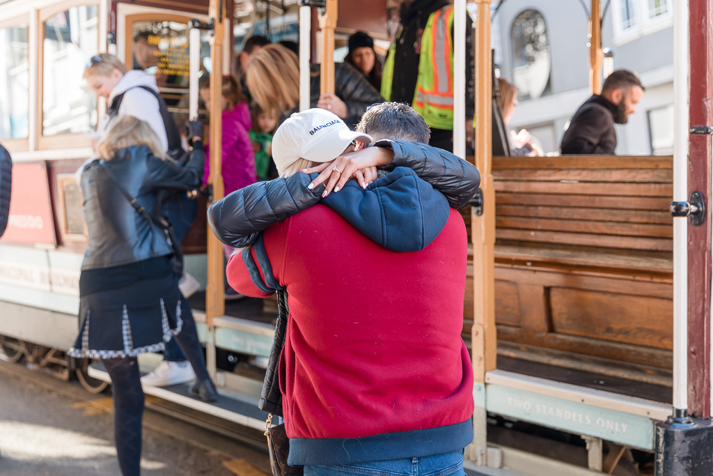 a big hug after they got engaged on the San Francisco trolley