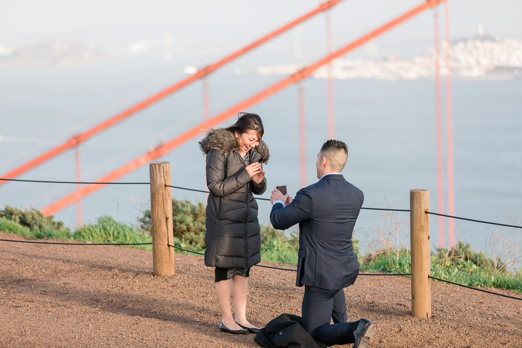 sweet candid surprise proposal moment in front of golden gate bridge